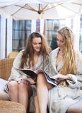 Two young women relaxing in the spa resort wearing toweling robe Stock Photography