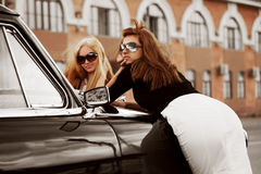 Two young women with a retro car Royalty Free Stock Photo