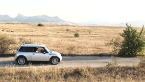 Two young women ride in a car against the backdrop of a mountain range