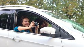 Two young women ride in a car and have fun. One of them takes a self photo on a film camera. Slow motion stock video