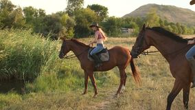 Two young women riding on a horse near the pond. Two young women riding on a brown horse near the pond stock video footage