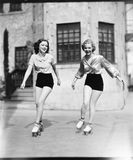 Two young women roller skating on the road and smiling Royalty Free Stock Photo
