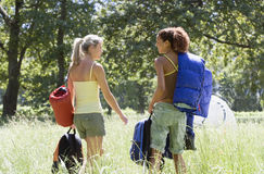 Two young women, with rucksacks and sleeping bags, departing on hiking trip in woodland clearing, rear view Stock Images