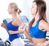 Two young women run on machine in the gym Stock Photos