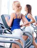 Two young women run on machine in the gym Stock Photo