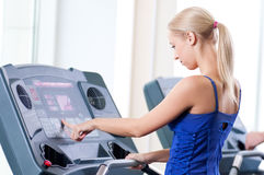 Two young women run on machine in the gym Royalty Free Stock Photo