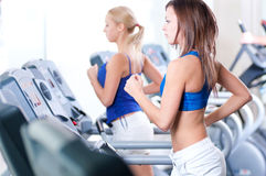 Two young women run on machine in the gym Royalty Free Stock Photography