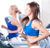 Two young women run on machine in the gym Stock Photography