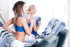 Two young women run on machine in the gym. Two young sporty women run on machine in the gym centre Royalty Free Stock Photos