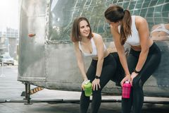 Two young women runners stand leaning against trailer, rest after training, drink water, communicate. Girls have break. royalty free stock photo