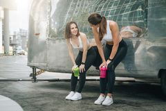 Two young women runners stand leaning against trailer, rest after training, drink water, communicate. Girls have break. stock photography