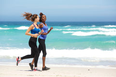 Two young women running along the beach Royalty Free Stock Photography