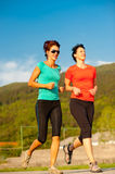 Two young women running outdoor. On a track Stock Photo