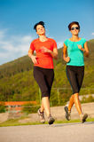 Two young women running outdoor. On a track Royalty Free Stock Photos
