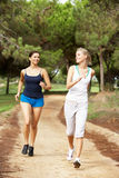 Two young women running in park stock photo