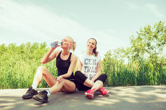 Two young women  seating outdoors in a park on sunny summer day Stock Image