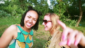 Two young women sending love to the camera. Two young women having fun while smiling and sending love to the camera in the park stock video footage