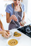 Two young women serving chickpeas and adding garlic into the soup. Royalty Free Stock Image
