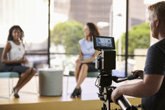 Two young women on set for TV interview, focus on foreground stock photo