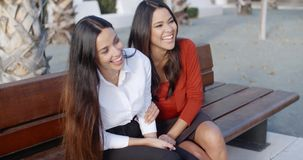 Two young women sharing a good joke. Two stylish young women sharing a good joke laughing as they sit together on an outdoor wooden bench in an urban park stock footage