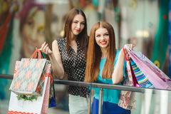 Two young women shop in a big supermarket. Two young women sharing their new purchases with each other. Image of two young women looking in the shopping bags Royalty Free Stock Photos