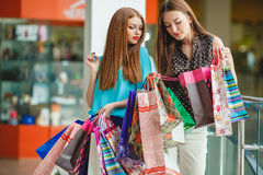 Two young women shop in a big supermarket. Stock Photos