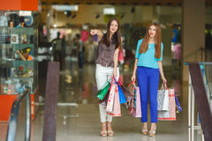 Two young women shop in a big supermarket. Royalty Free Stock Photo