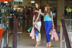 Two young women shop in a big supermarket. Royalty Free Stock Image