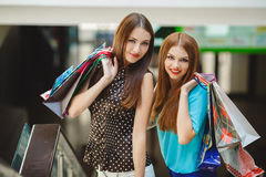 Two young women shop in a big supermarket. Two young women sharing their new purchases with each other. Image of two young women looking in the shopping bags Stock Images