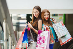 Two young women shop in a big supermarket. Two young women sharing their new purchases with each other. Image of two young women looking in the shopping bags Royalty Free Stock Image