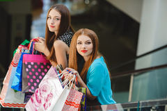 Two young women shop in a big supermarket. Two young women sharing their new purchases with each other. Image of two young women looking in the shopping bags Royalty Free Stock Photography