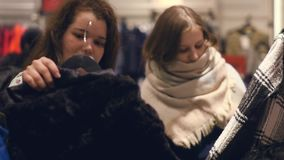 Two young women shop at the store choosing warm winter clothes. Slow motion stock footage