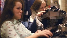Two young women shop at the store choosing warm winter clothes. Slow motion stock video