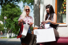 Two happy fashion women with shopping bags walking in city street Royalty Free Stock Images