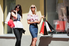 Two young women shopping. Two young women with shopping bags against of store windows Royalty Free Stock Photography