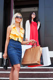 Two young women shopping. Two young woman with shopping bags at the mall doorway Stock Photography