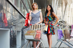 Two young women shopping. Young women with shopping cart in supermarket Royalty Free Stock Photography