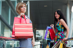 Two young women with shopping bags. Royalty Free Stock Photos
