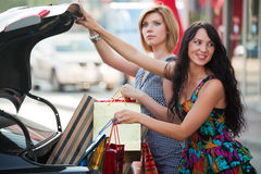 Two young fashion women with shopping bags next to car trunk Stock Photography