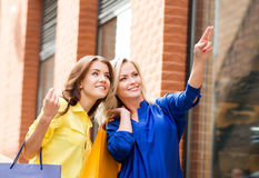 Two young women with shopping bags. Two beautiful women shopping in the city center. Blond is pointing at some clothing store Stock Photography