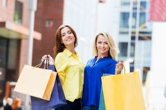 Two young women with shopping bags. Two beautiful women shopping in the city center. Blond is pointing at some clothing store Royalty Free Stock Image