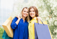 Two young women with shopping bags. Two beautiful women shopping in the city center. Blond is pointing at some clothing store Royalty Free Stock Photos