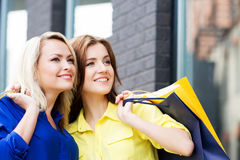 Two young women with shopping bags. Two beautiful women shopping in the city center. Blond is pointing at some clothing store Royalty Free Stock Images