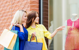 Two young women with shopping bags. Two beautiful young women looking at pink dress in showcase Stock Photo