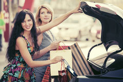 Two young women with shopping bags on the car parking Royalty Free Stock Images