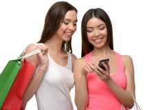 Two young women after shopping with bags and phone. Two young women with colorful paper bags. They using phone. Concept for shop sales. Isolated on white Royalty Free Stock Photography