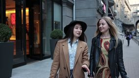 Two young women with shopping bags walking in city. Beautiful female friends communicating on the city street while walking on sidewalk for shopping. Two smiling stock footage