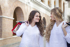 Two young women with shopping bags walking on the street Royalty Free Stock Image