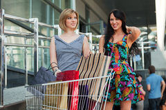 Two young women with shopping cart. Royalty Free Stock Images