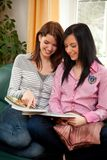 Two young women while shopping in the catalog Royalty Free Stock Image